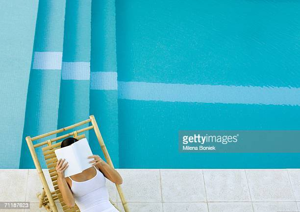 Woman sitting in lounge chair by pool, reading, high angle view