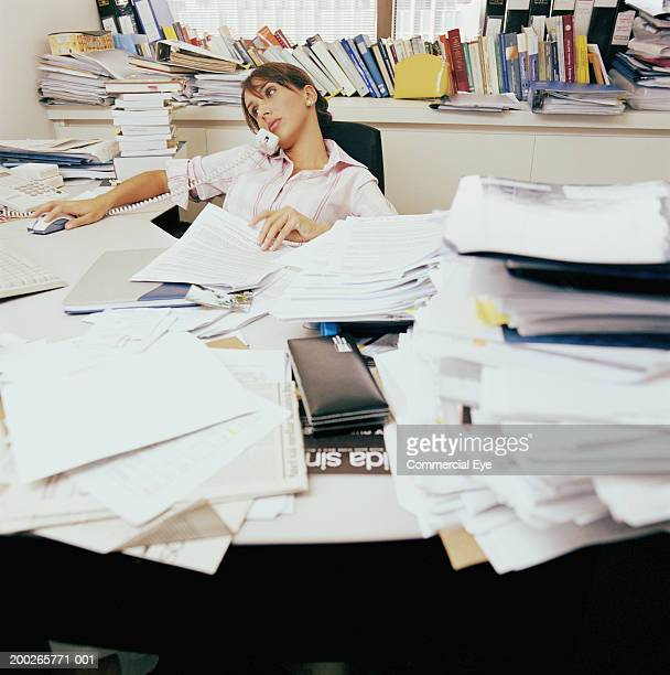 Woman sitting in messy office using phone