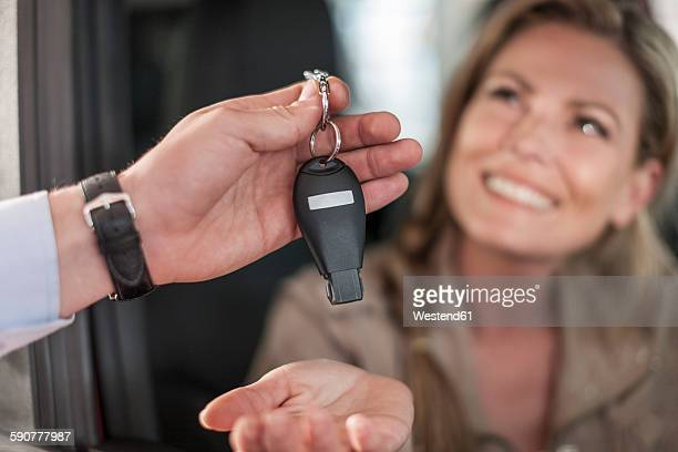 Woman sitting in new car receiving key