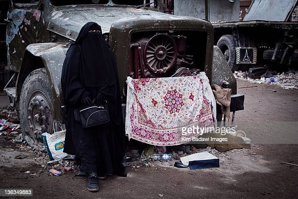 Woman sitting in no man's land between AntiMubarak and ProMubarak forces on February 6 2011 in Tahrir Square in downtown Cairo Egypt