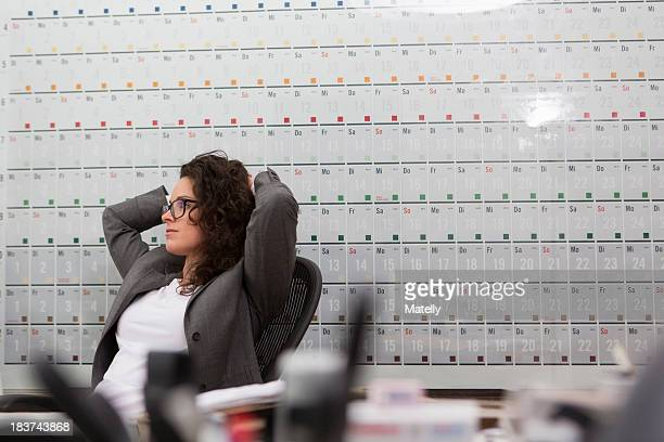 Woman sitting in office chair in front of large wall calendar