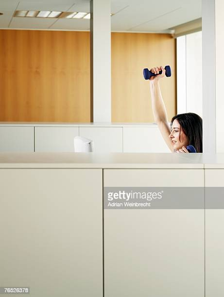 Woman sitting in office lifting weights, side view