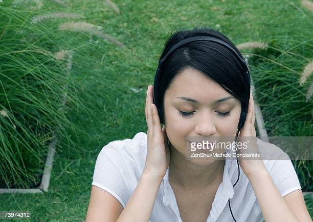 Woman sitting in ornamental garden, listening to headphones