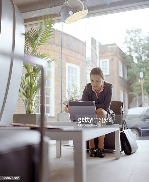 Woman sitting in outdoor lounge working alone