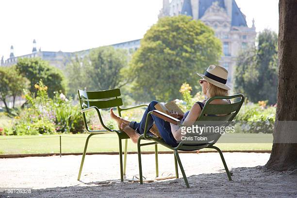 Woman sitting in park reading a book