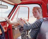 Woman sitting in pick-up truck, resting feet on dashboard, portrait