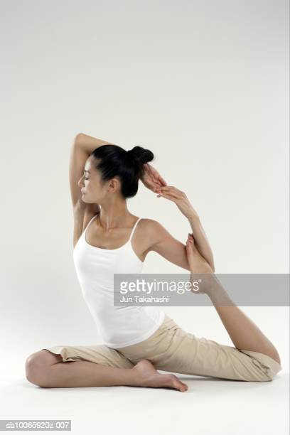 Woman sitting in pigeon pose, eyes closed