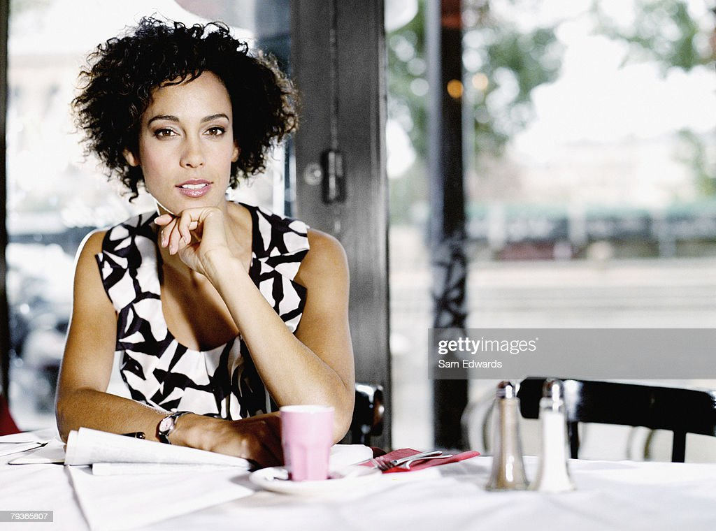 Woman sitting in restaurant with paperwork : Stock Photo