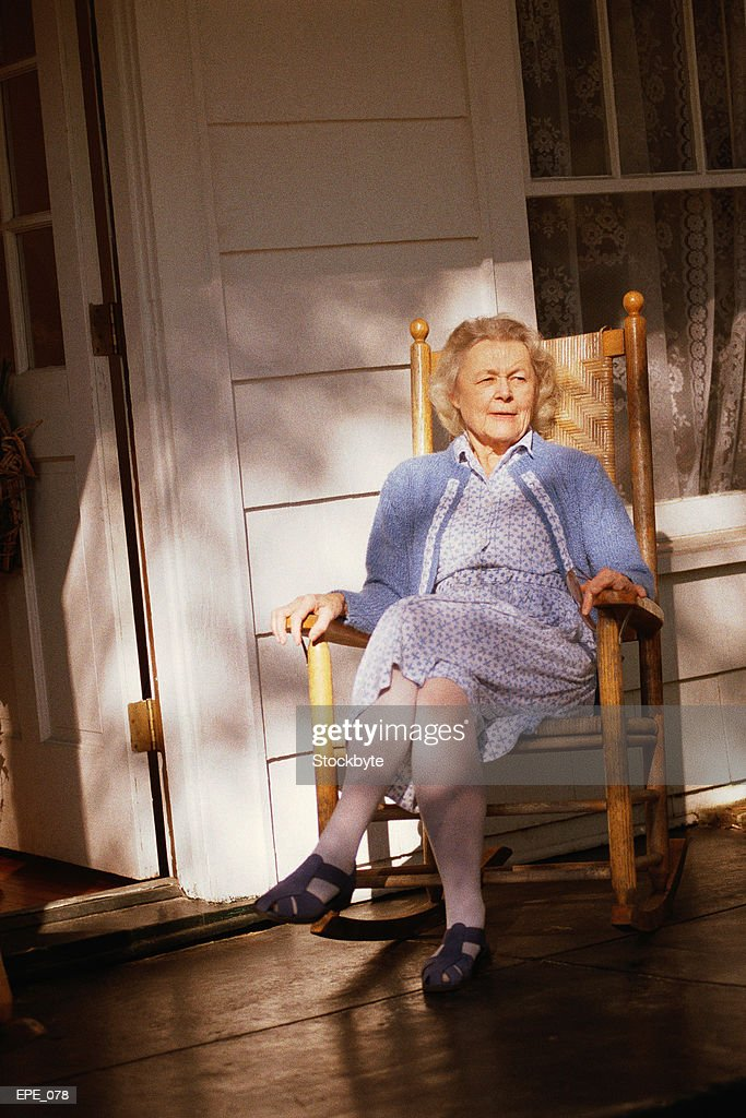 woman sitting in rocking chair on porch stock photo Old Rocking Chair On Porch Red Rocking Chair On Porch