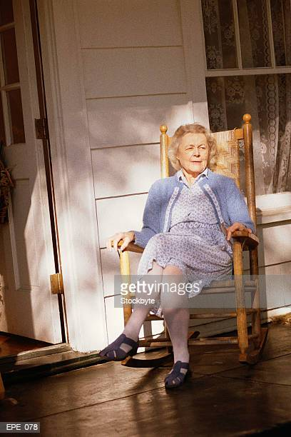 Woman sitting in rocking chair on porch