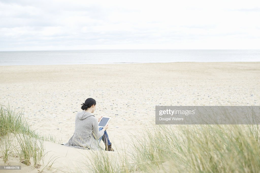 Woman sitting in sand dunes with digital tablet.