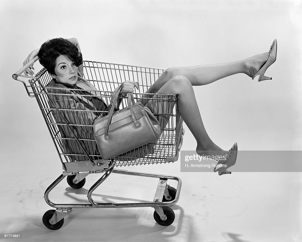 Woman sitting in shopping cart. : Stock Photo