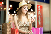 Portrait of beautiful happy woman wearing hat and dress sitting in shopping centre with colorful shopping bags, using smartphone app, looking at screen, messaging, smiling. Red sale sign on background