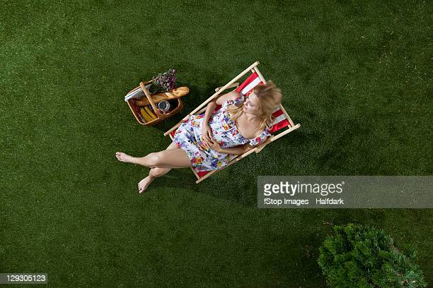 A woman sitting in the sun on a grass in a park with a picnic basket, overhead view