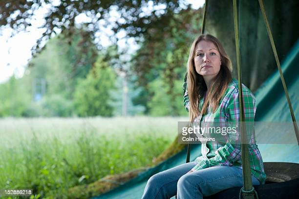 Woman sitting in tire swing outdoors