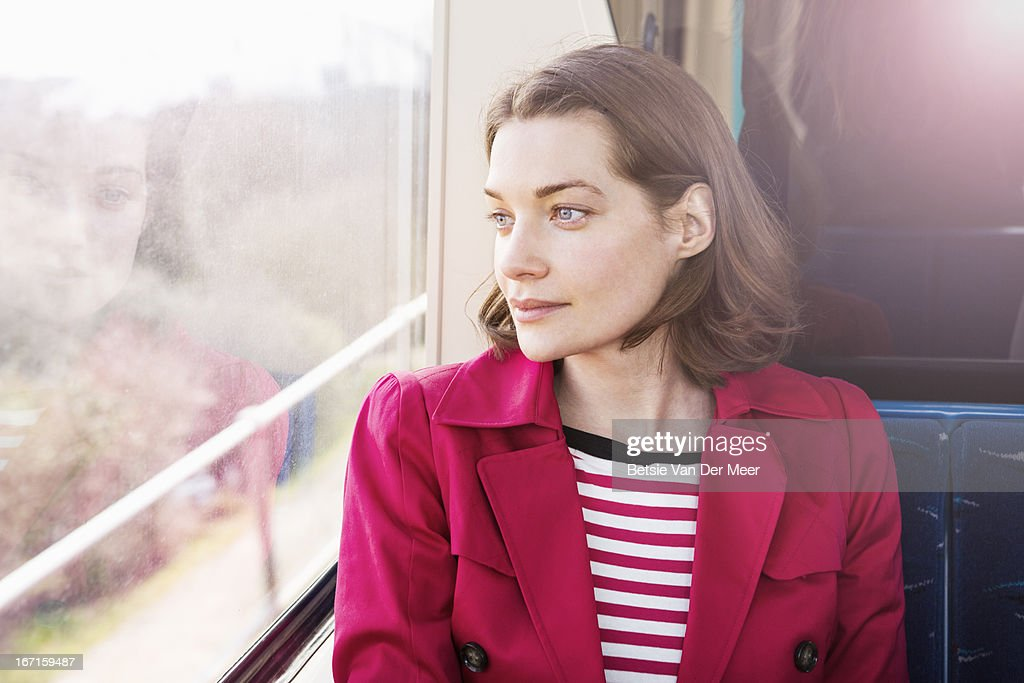 Woman sitting in train looking out of window.