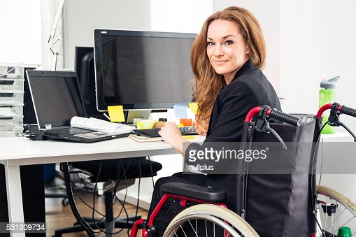 woman sitting in wheelchair working in modern office