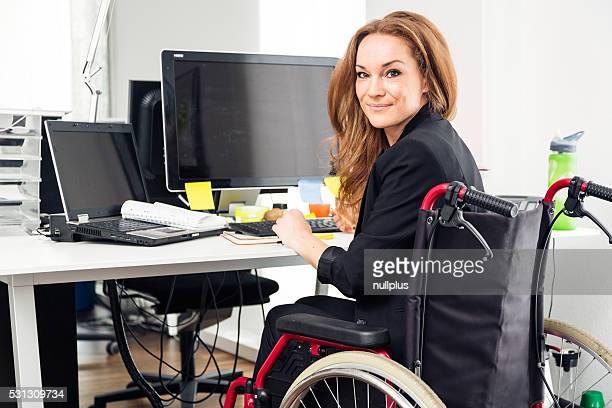 Frau sitzt im Rollstuhl der Arbeit in modernen Büro