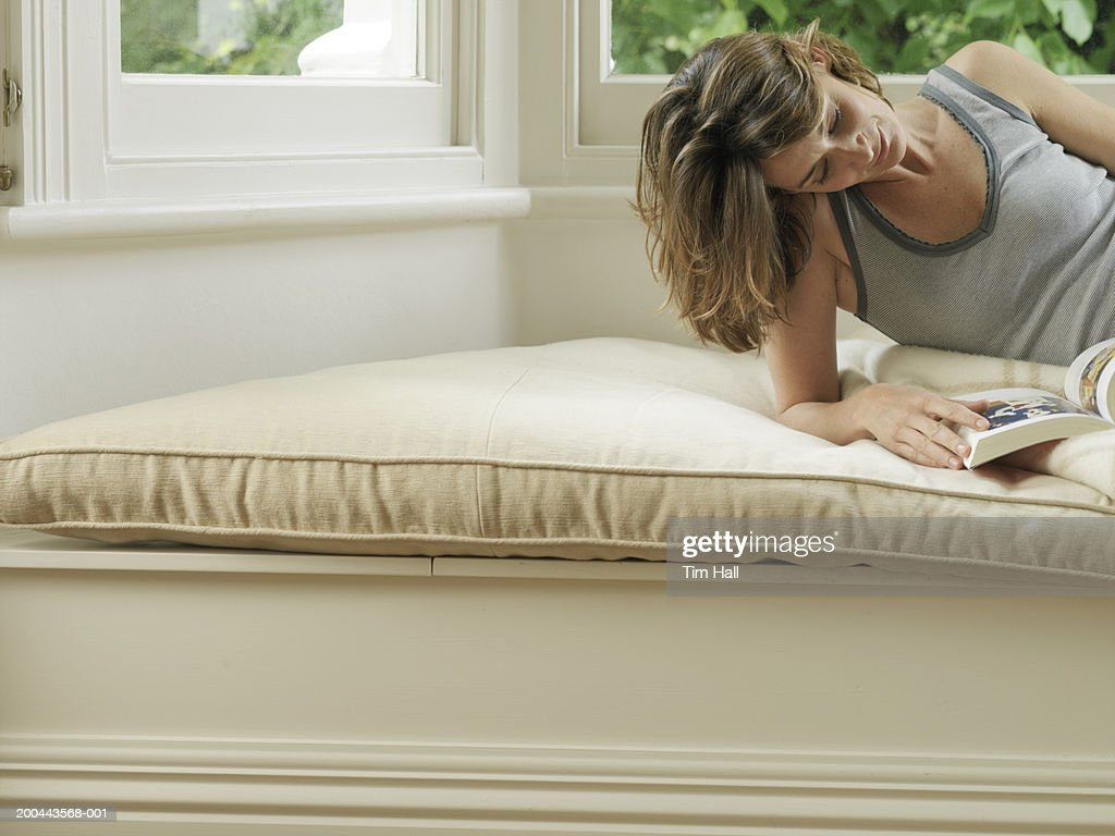Woman sitting in window alcove reading book
