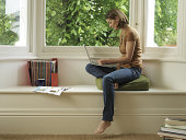 Woman sitting in window alcove using laptop, side view