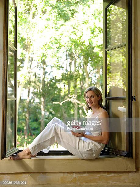Woman sitting in window eating bowl of fruit and yoghurt, portrait