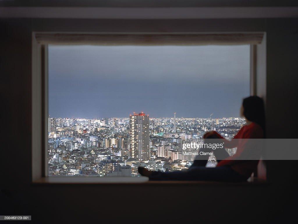 Woman sitting in window, looking at skyline, (focus on skyline) : Stock Photo