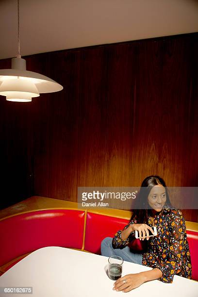 Woman sitting in wood panelled booth holding smartphone looking away smiling