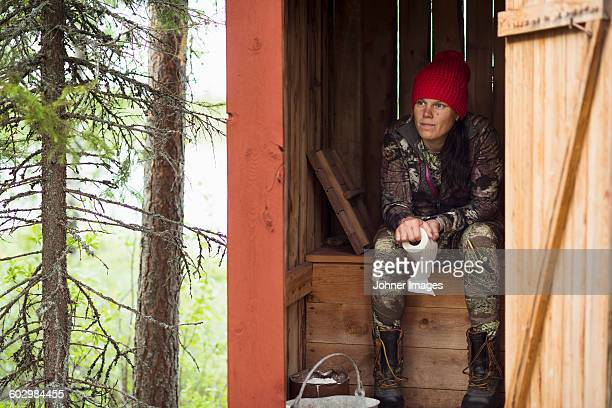 Woman sitting in wooden outhouse