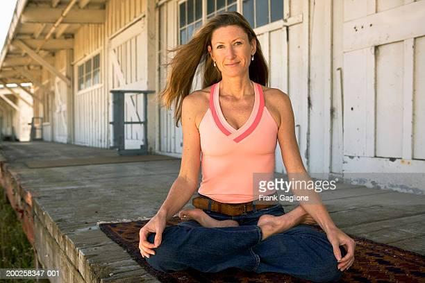 Woman sitting in yoga lotus pose, smiling, portrait