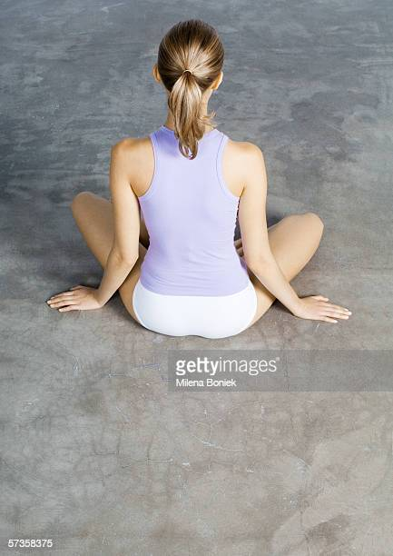 Woman sitting indian style on floor, rear view