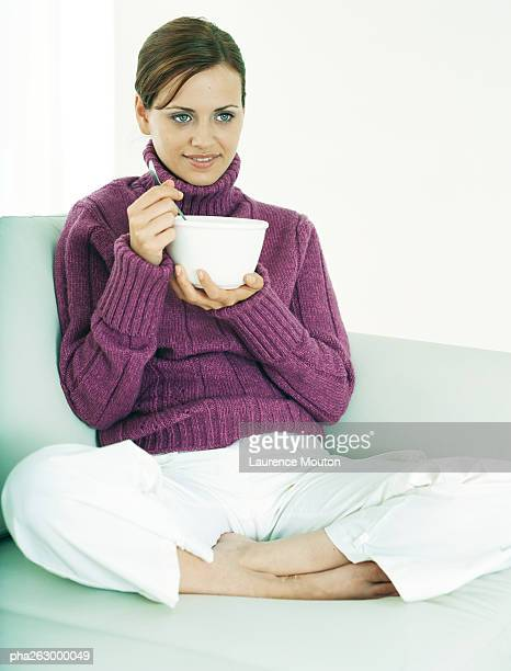 Woman sitting indian style on sofa holding bowl and utensil