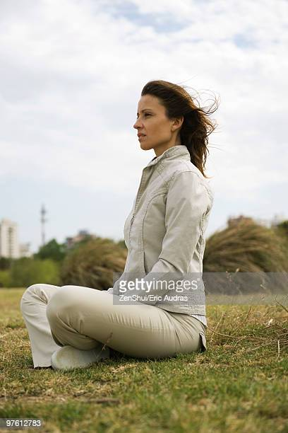 Woman sitting indian style outdoors looking away contemplatively