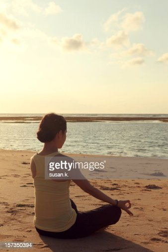 A woman sitting lotus pose by the beach. : Stock Photo