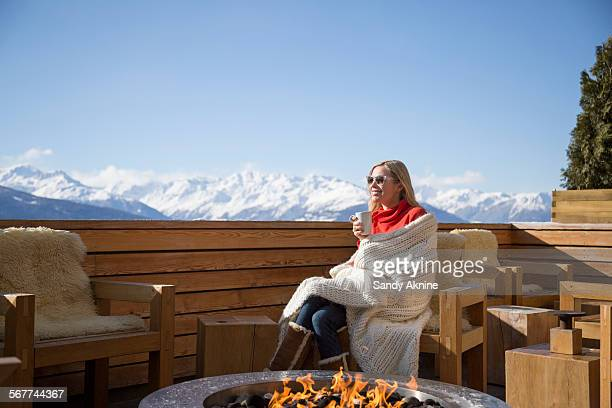 Woman sitting near fire pit on the terrace of a hotel, Crans-Montana, Swiss Alps, Switzerland