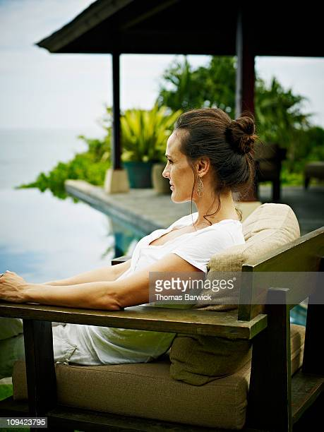 Woman sitting near infinity pool at resort
