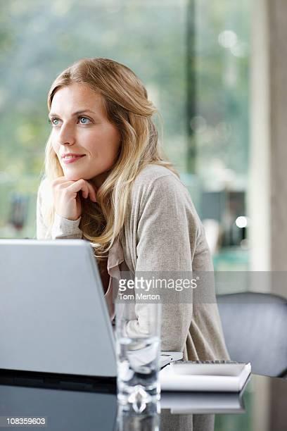 Woman sitting near laptop daydreaming