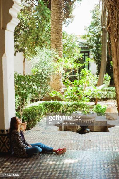 Woman sitting near the entrance to garden from riad