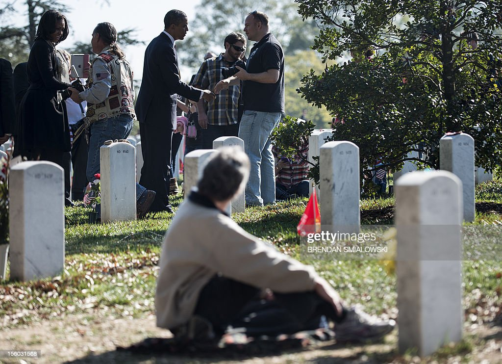 A woman sitting next to a grave watches as US President Barack Obama and first lady Michelle Obama greet people while visiting Section 60 of Arlington National Cemetery on Veterans' Day November 11, 2012 in Arlington, Virginia. Obama visited the area of the cemetery which is where many who died while serving in the War on Terrorism, the war in Iraq and the war in Afghanistan are laid to rest. AFP PHOTO/Brendan SMIALOWSKI