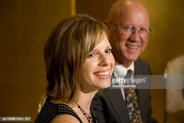Woman sitting next to man at wedding party, smiling, close up