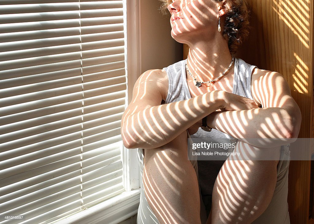Woman sitting next to miniblinds with arms folded