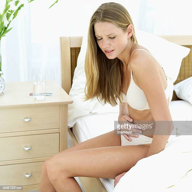 woman sitting on a bed in her underwear holding her stomach in pain