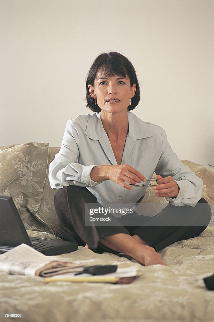 Woman sitting on a bed : Stock Photo