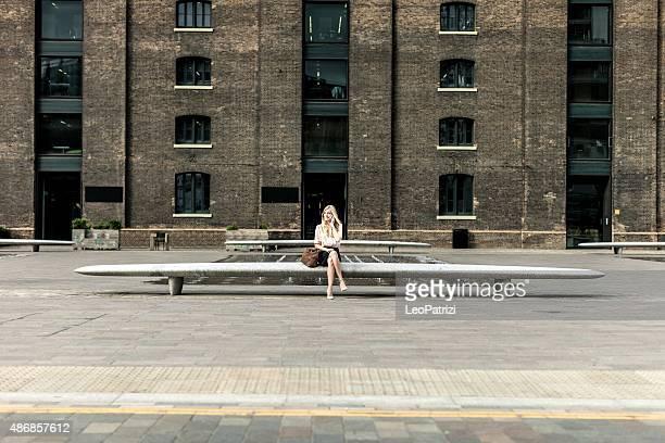 Femme assise sur un banc, avec un appel