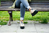 Woman sitting on a bench in a park. Only legs
