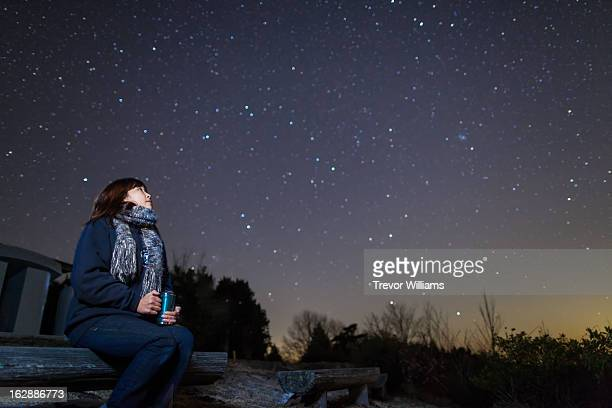 A woman sitting on a bench looking up at stars
