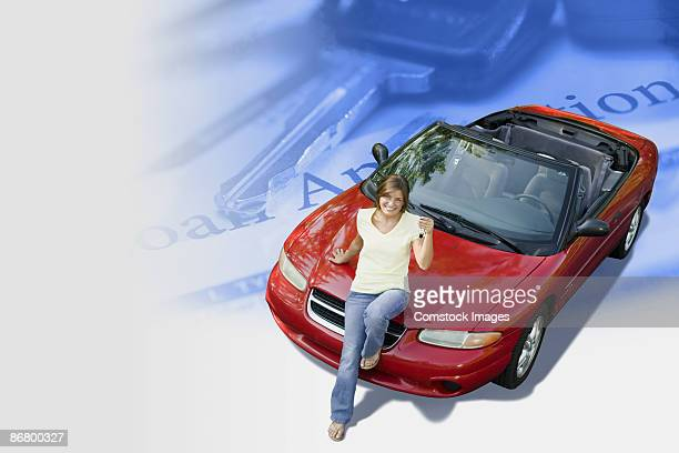 Woman sitting on a car with paperwork and keys
