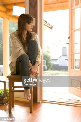 Woman sitting on a chair, by the window : Stock Photo