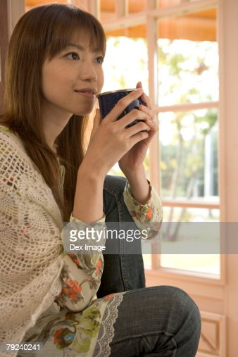 Woman sitting on a chair with a cup, by the window : Stock Photo