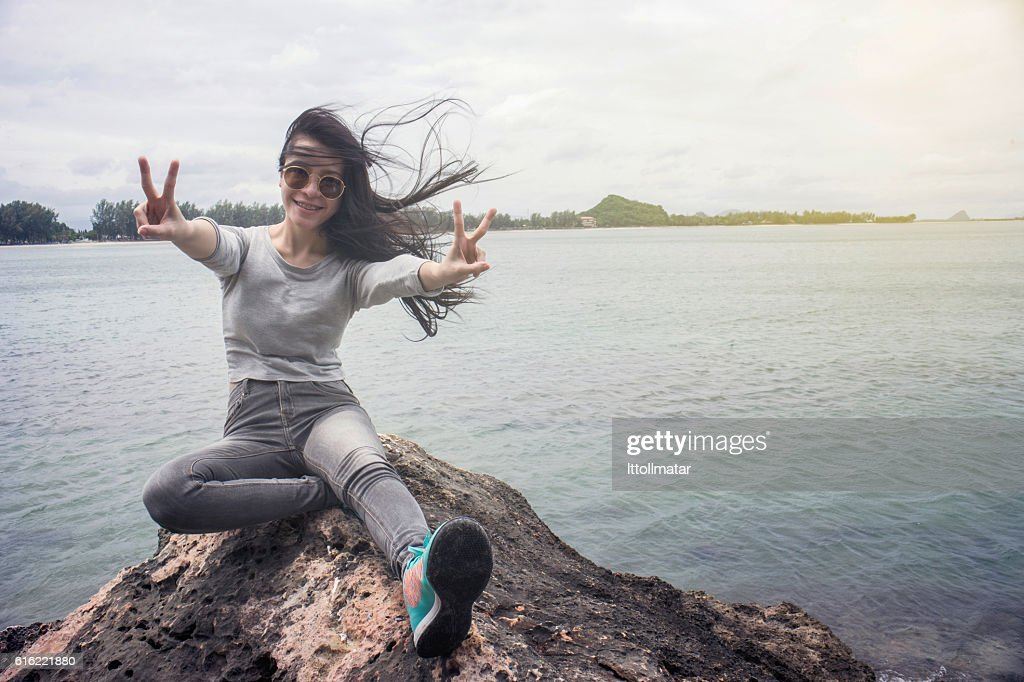 Woman sitting on a cliff hill top near the sea : Stock Photo
