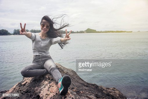 Woman sitting on a cliff hill top near the sea : Bildbanksbilder